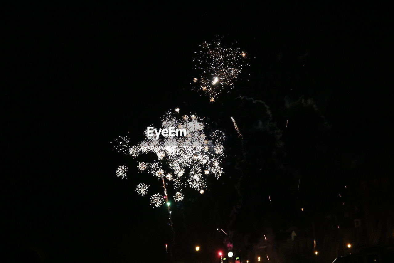 night, firework display, celebration, firework - man made object, exploding, illuminated, event, low angle view, glowing, long exposure, firework, blurred motion, arts culture and entertainment, motion, outdoors, smoke - physical structure, sky, no people, tree