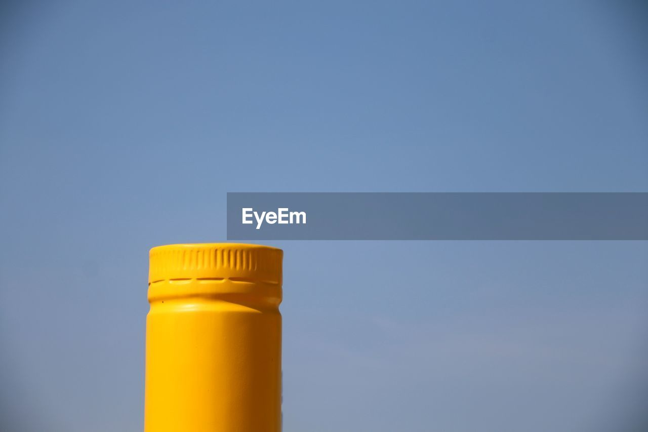 LOW ANGLE VIEW OF YELLOW BOTTLE ON BLUE SKY