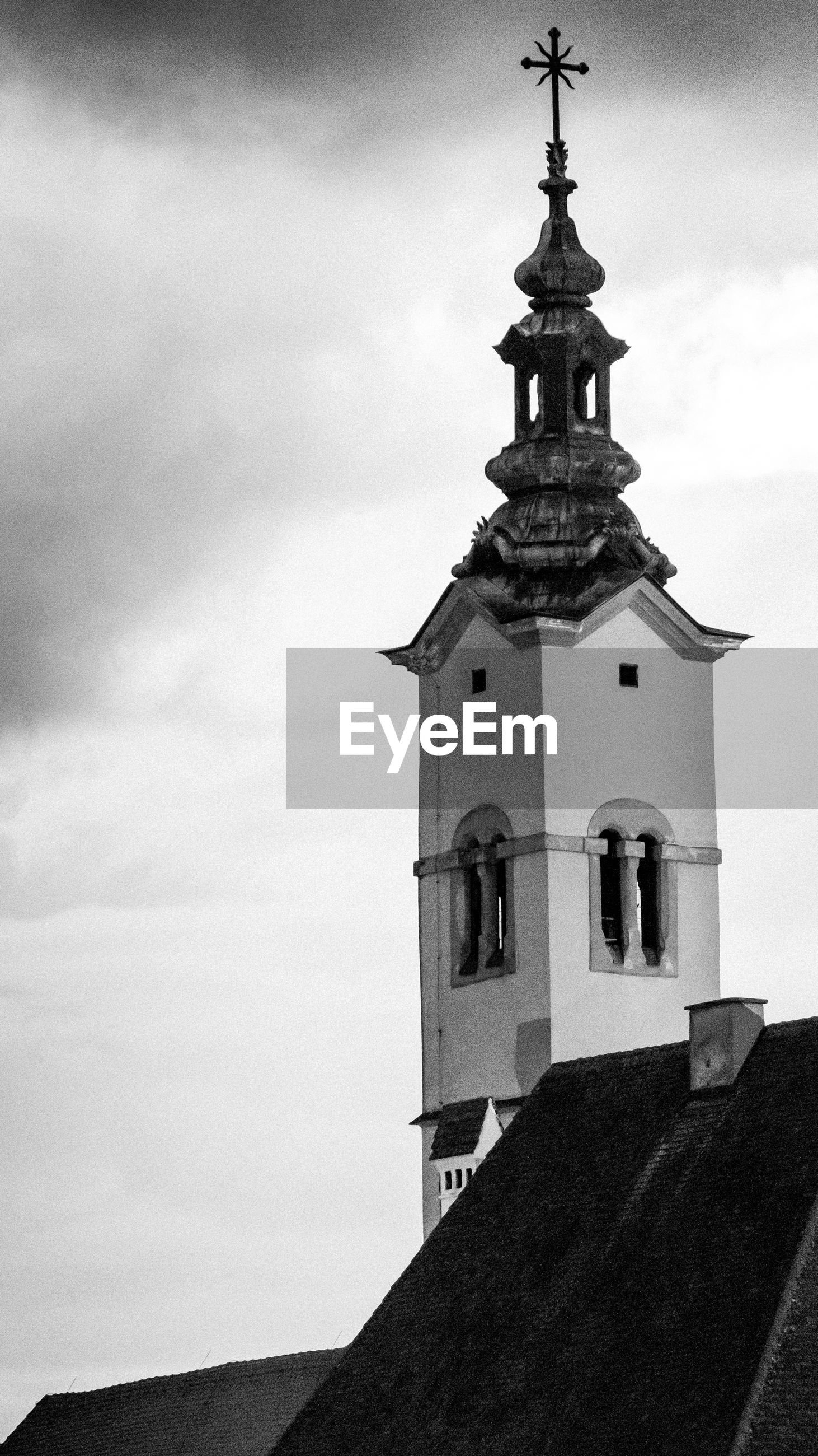 religion, sky, place of worship, spirituality, cloud - sky, architecture, tower, built structure, low angle view, bell tower, no people, day, outdoors, bell, cross, building exterior, history, clock tower, travel destinations, nature, clock