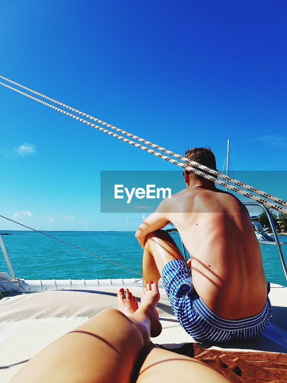 Couple Sitting On Yacht Against Clear Sky