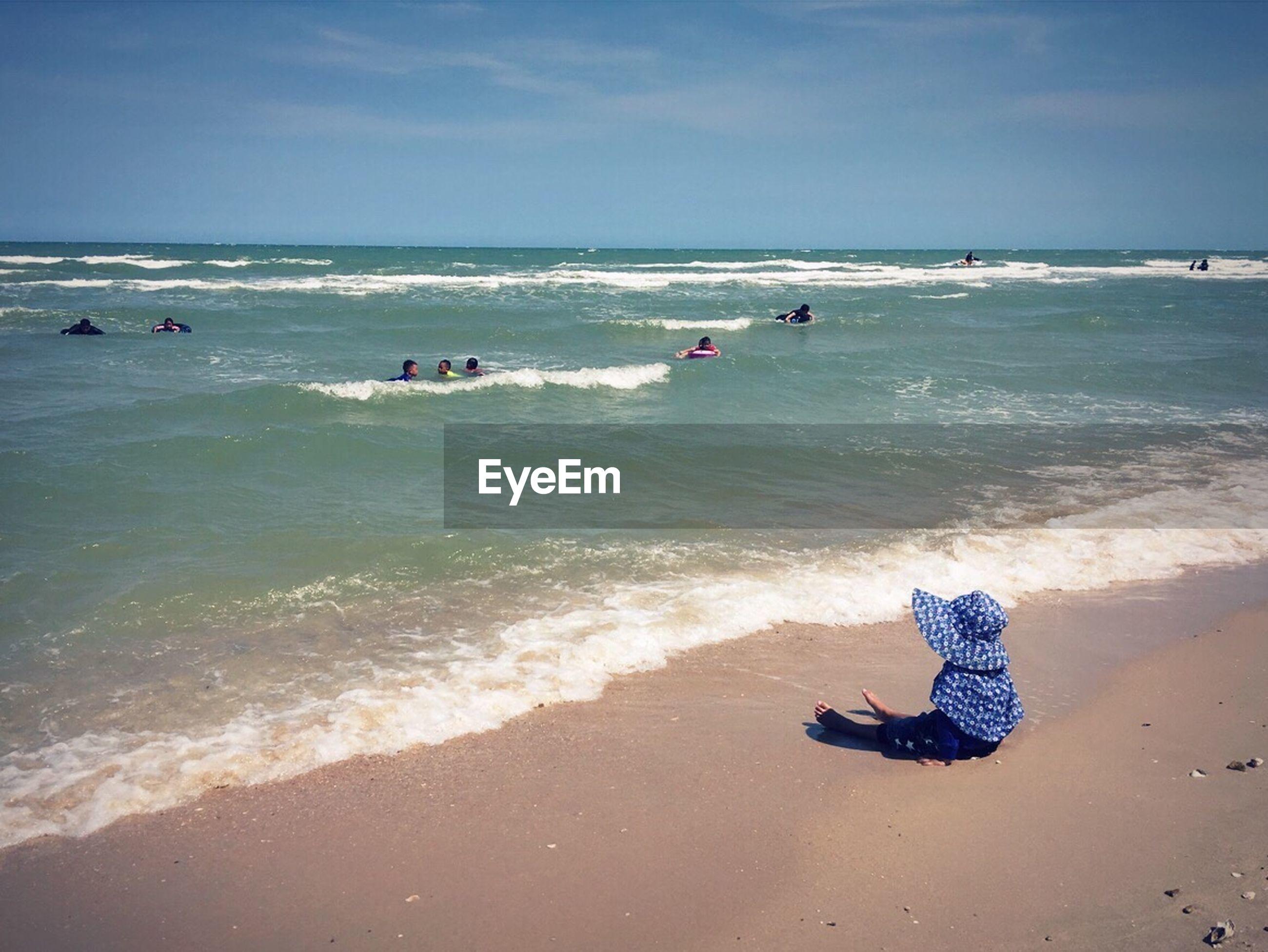 Girl sitting on shore against sky