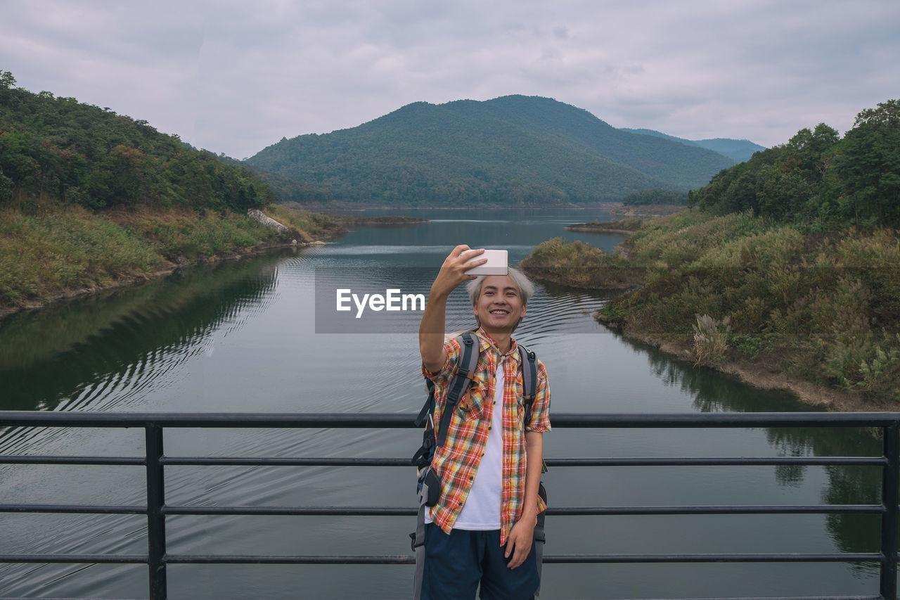 Man taking selfie while standing against lake