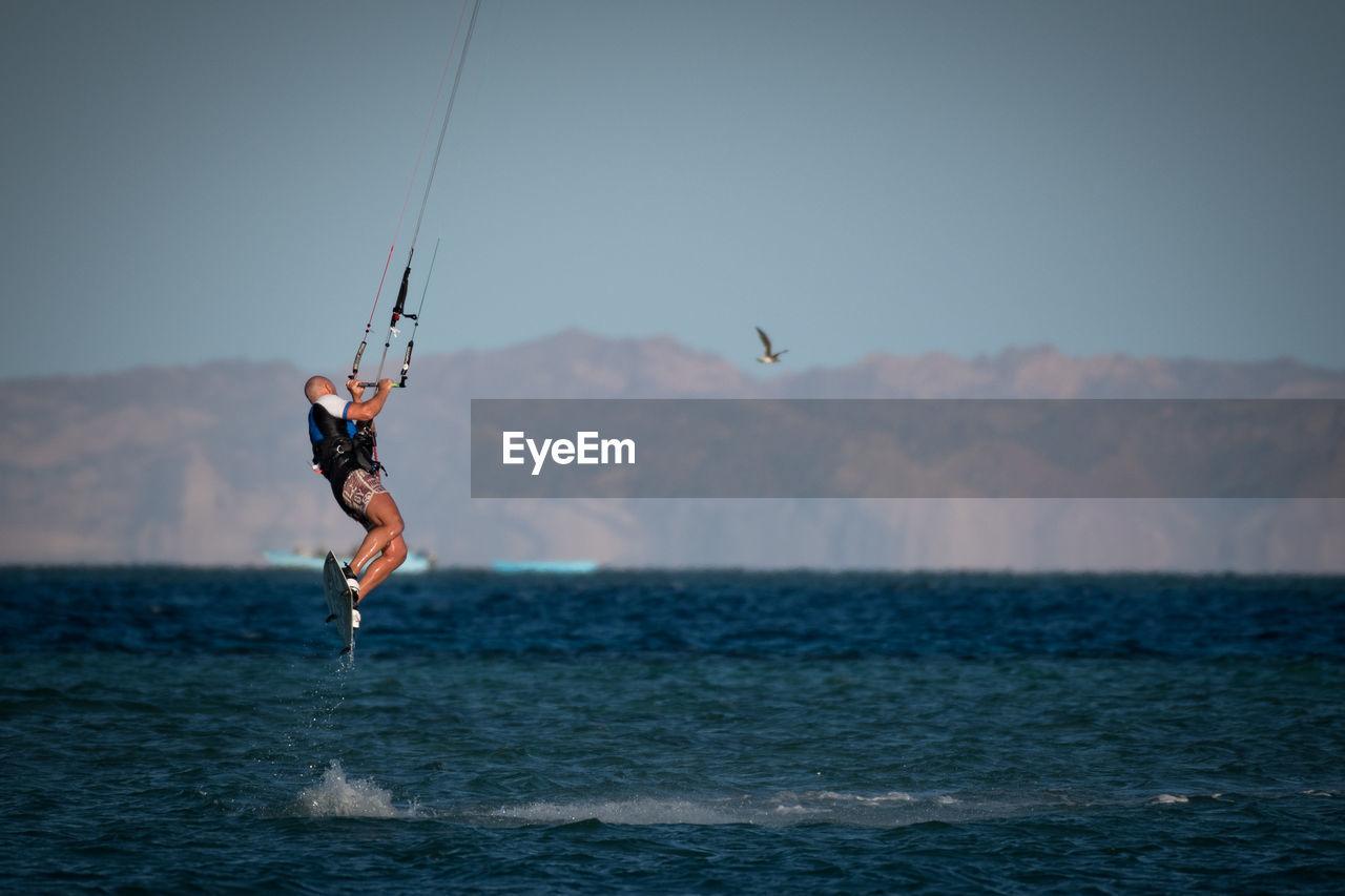 Man kiteboarding over sea against sky