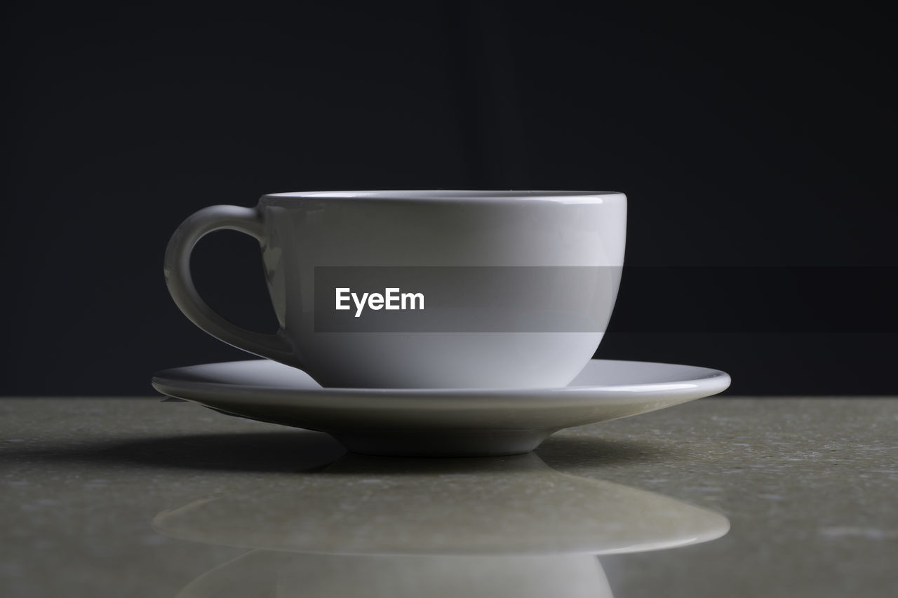 CLOSE-UP OF COFFEE CUP AND SPOON ON TABLE