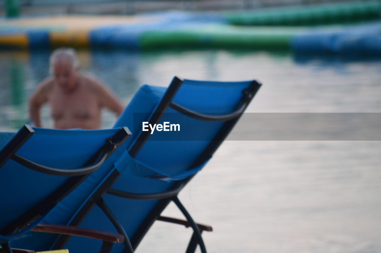Blue chairs against lake