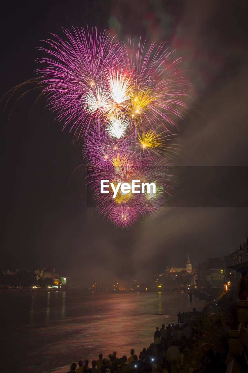 illuminated, firework, night, firework display, celebration, exploding, water, event, arts culture and entertainment, motion, sky, architecture, light, glowing, long exposure, no people, building exterior, multi colored, firework - man made object, outdoors, sparks, cityscape