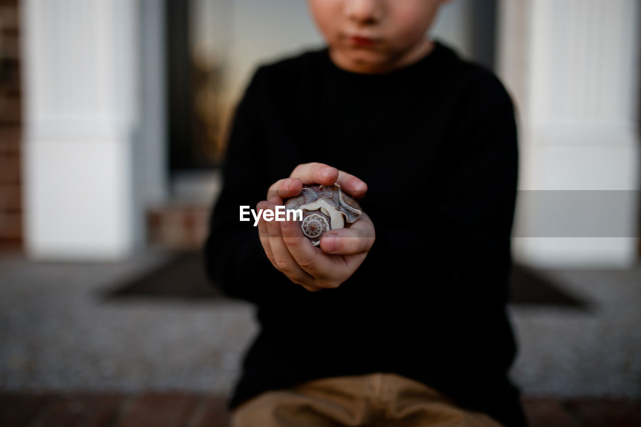 Midsection of boy holding seashell