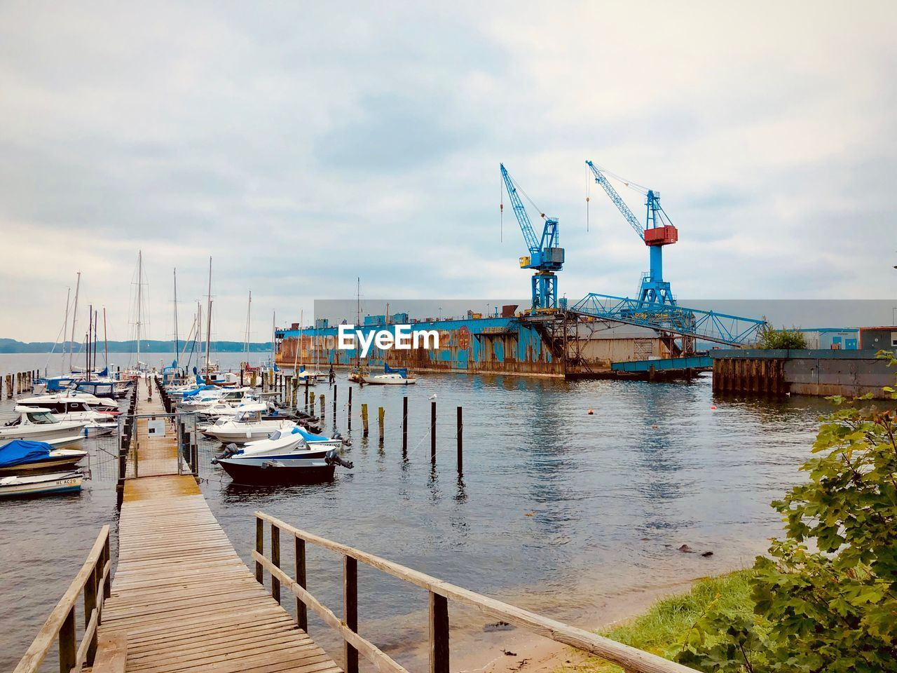 water, transportation, cloud - sky, nautical vessel, sky, mode of transportation, pier, moored, harbor, no people, architecture, nature, day, sea, built structure, wood - material, building exterior, outdoors, machinery, port, sailboat, wooden post, fishing boat, marina