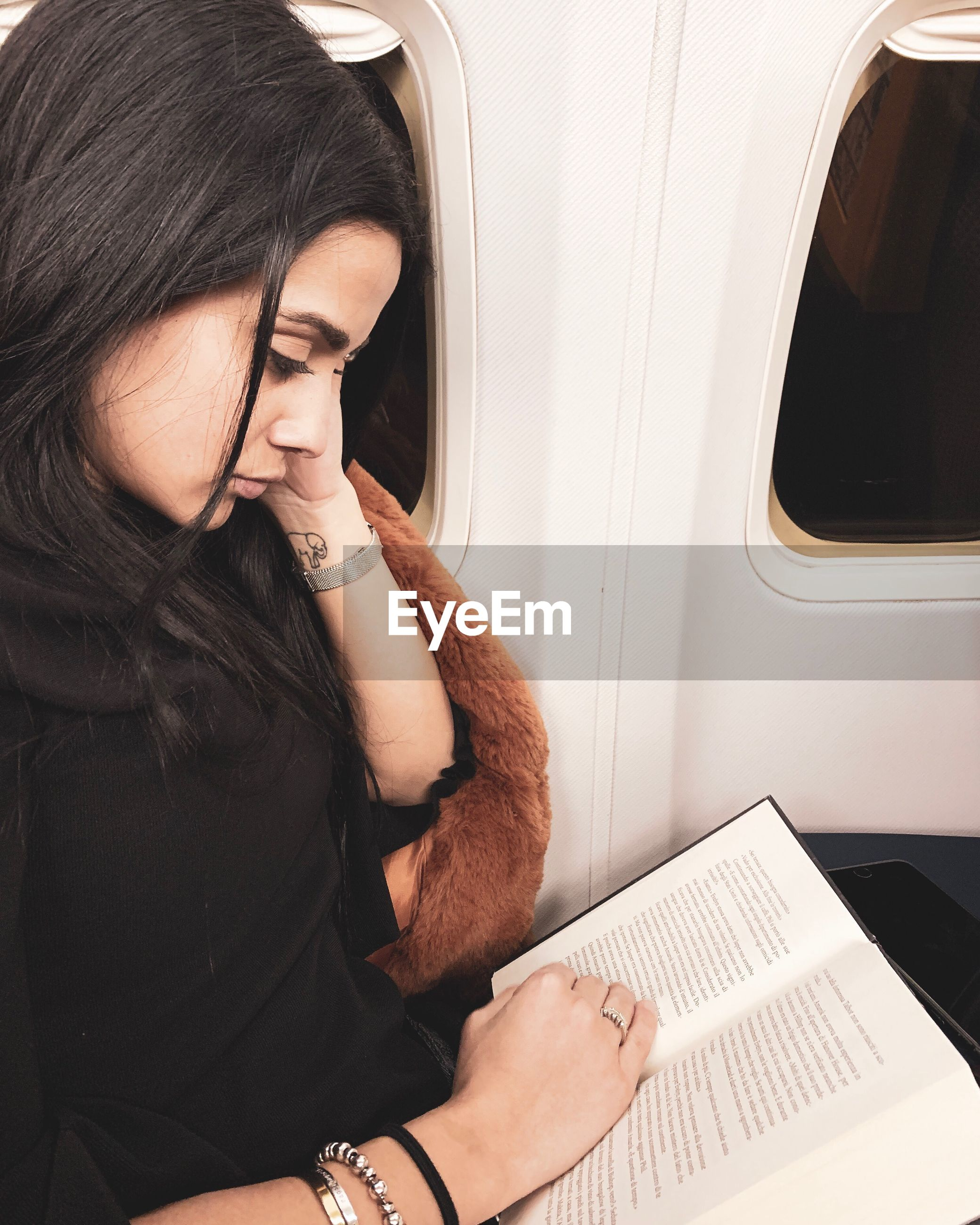 Woman reading book while sitting in airplane