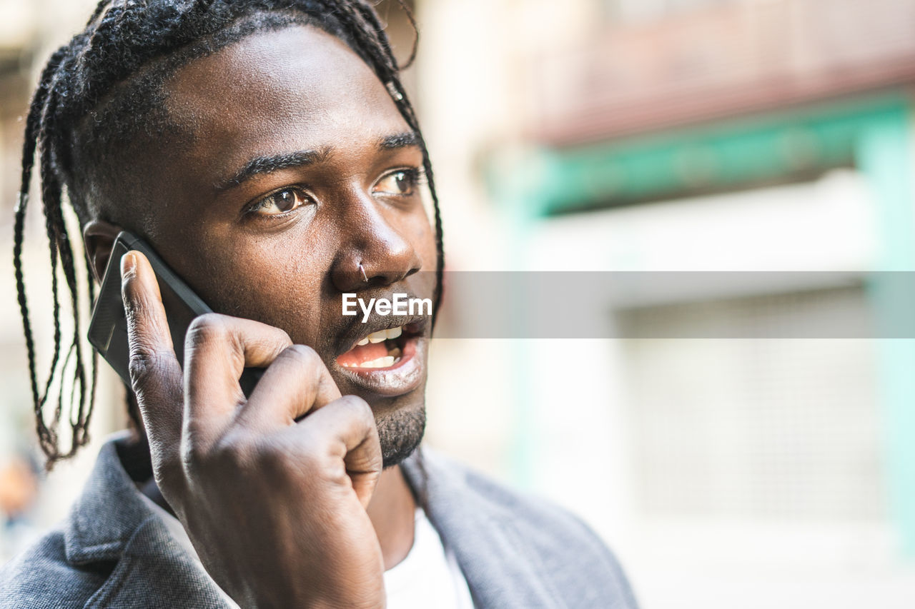 PORTRAIT OF YOUNG MAN USING PHONE