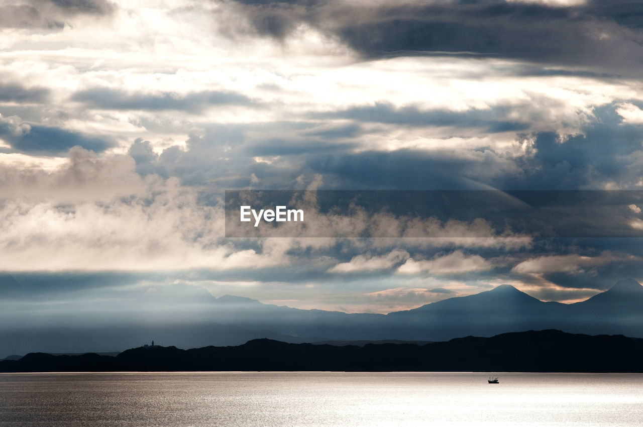 Scenic View Of River Against Cloudy Sky During Sunny Day