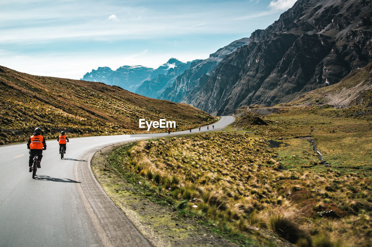 Rear view of people riding bicycles on road against mountains