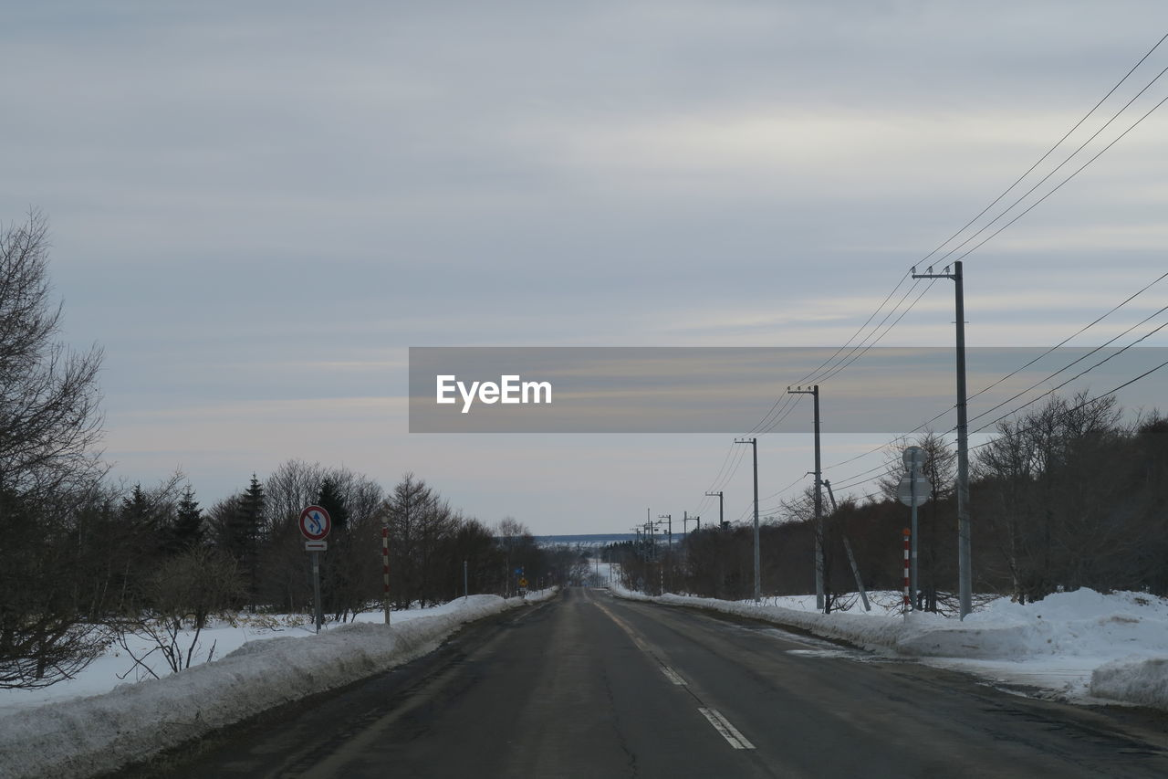 cold temperature, winter, snow, sky, road, transportation, direction, the way forward, cloud - sky, diminishing perspective, nature, no people, tree, covering, vanishing point, plant, electricity, scenics - nature, frozen