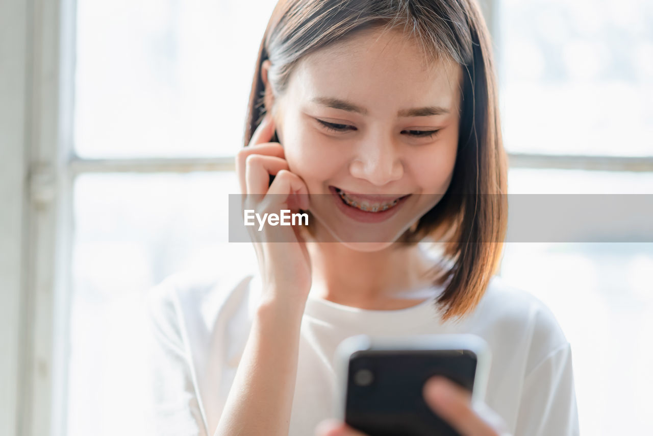 Smiling young woman using mobile phone indoors
