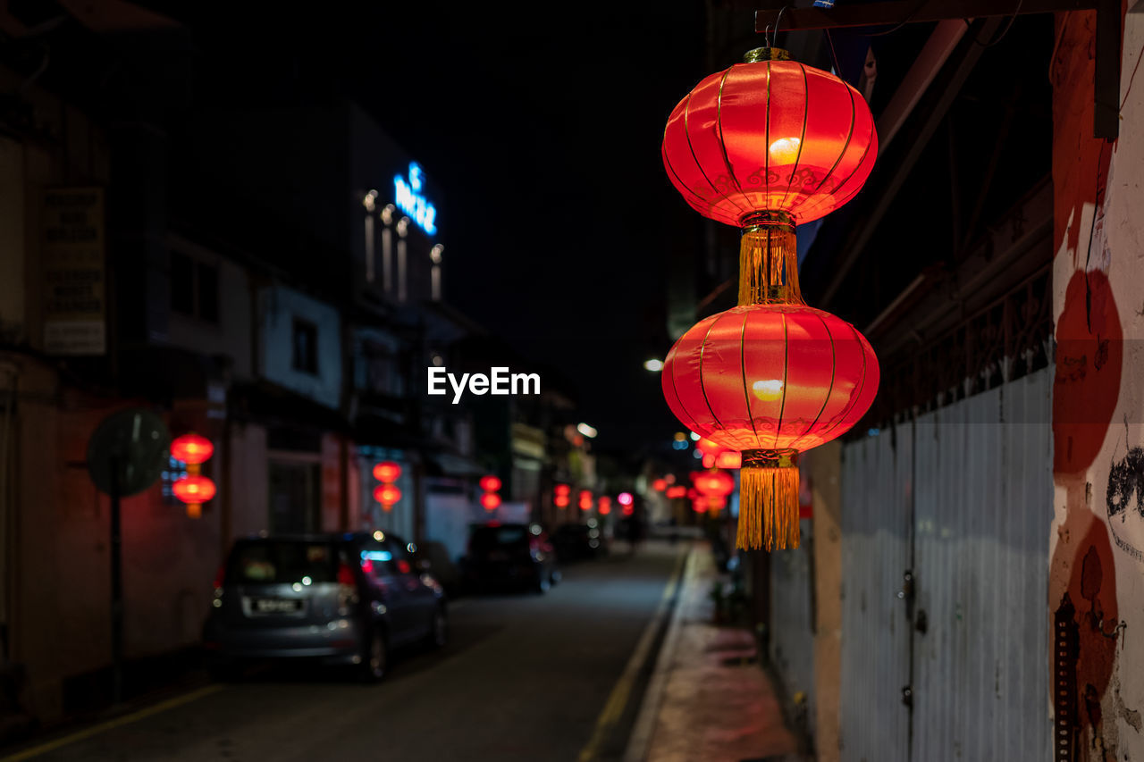 illuminated, night, red, lighting equipment, architecture, city, building exterior, built structure, street, transportation, lantern, mode of transportation, motor vehicle, car, focus on foreground, land vehicle, no people, decoration, chinese lantern, road, outdoors, chinese new year