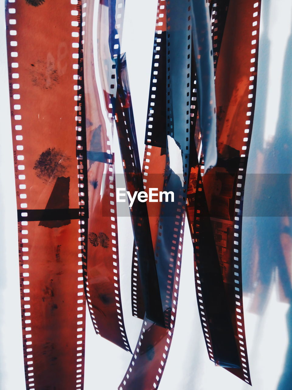 Close-up of film reels hanging against white background
