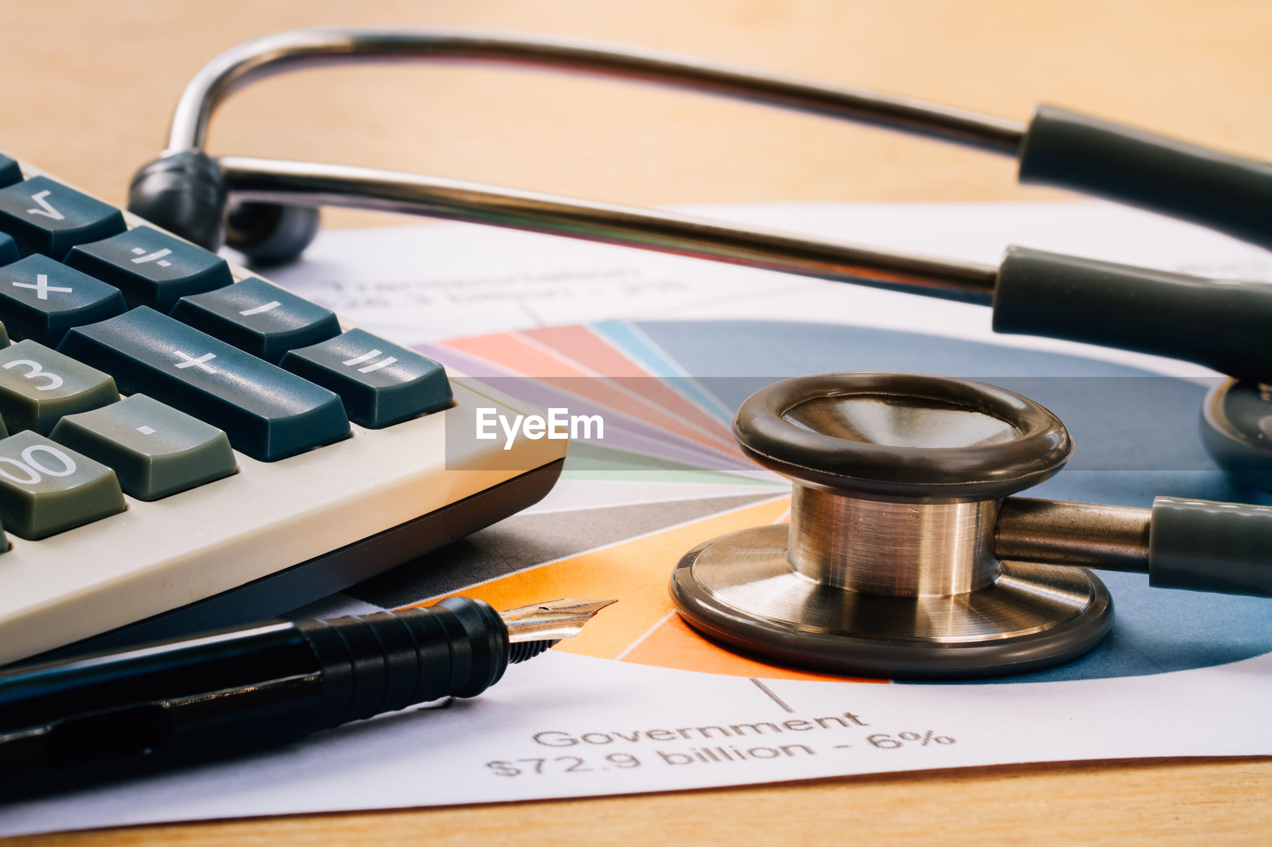 Close-up of stethoscope with calculator and document on table