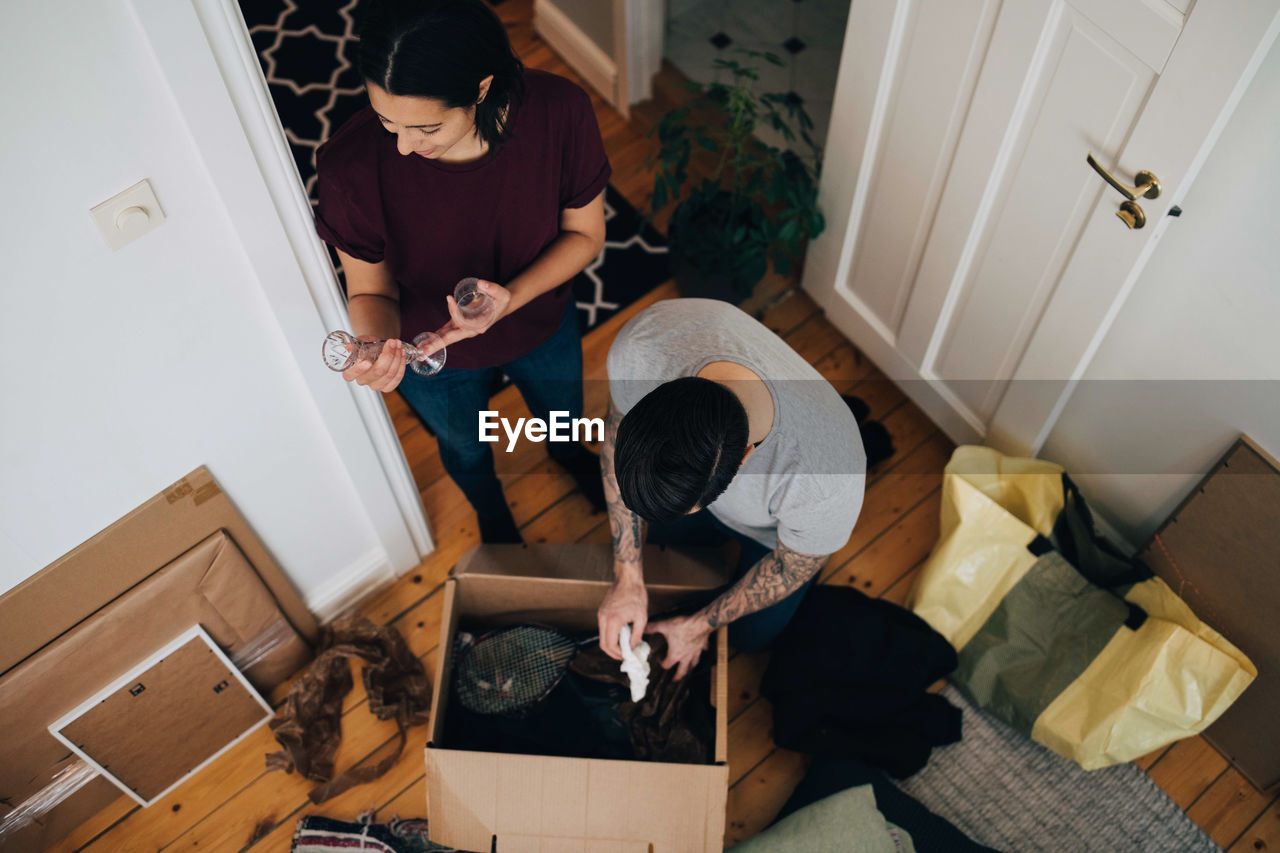 real people, high angle view, indoors, casual clothing, lifestyles, full length, home interior, people, two people, young adult, domestic room, sitting, togetherness, three quarter length, holding, men, standing, young men, flooring, leisure activity
