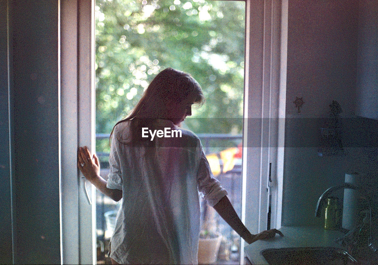 window, looking through window, one person, indoors, standing, day, real people, lifestyles, women, domestic room, one woman only, young adult, one young woman only, window washer, adult, people, adults only