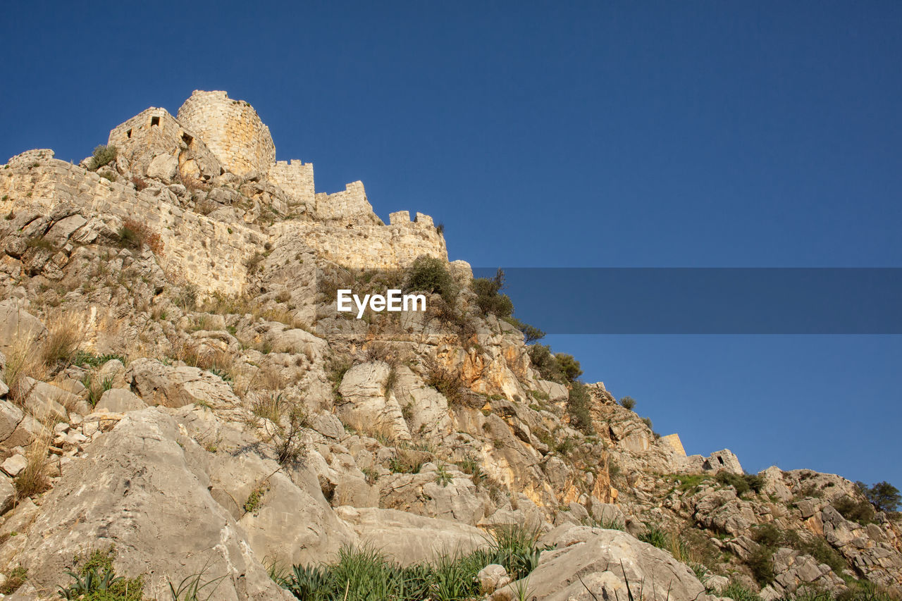 sky, rock, clear sky, mountain, low angle view, rock - object, beauty in nature, nature, solid, rock formation, no people, blue, copy space, day, tranquility, scenics - nature, land, tranquil scene, geology, environment, outdoors, mountain peak, formation