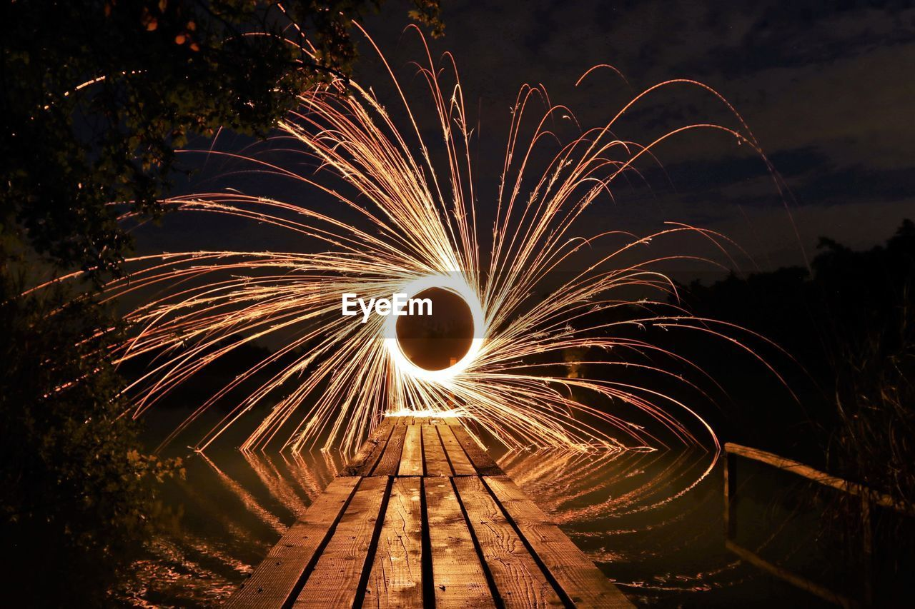 Illuminated wire wool spinning over lake at night