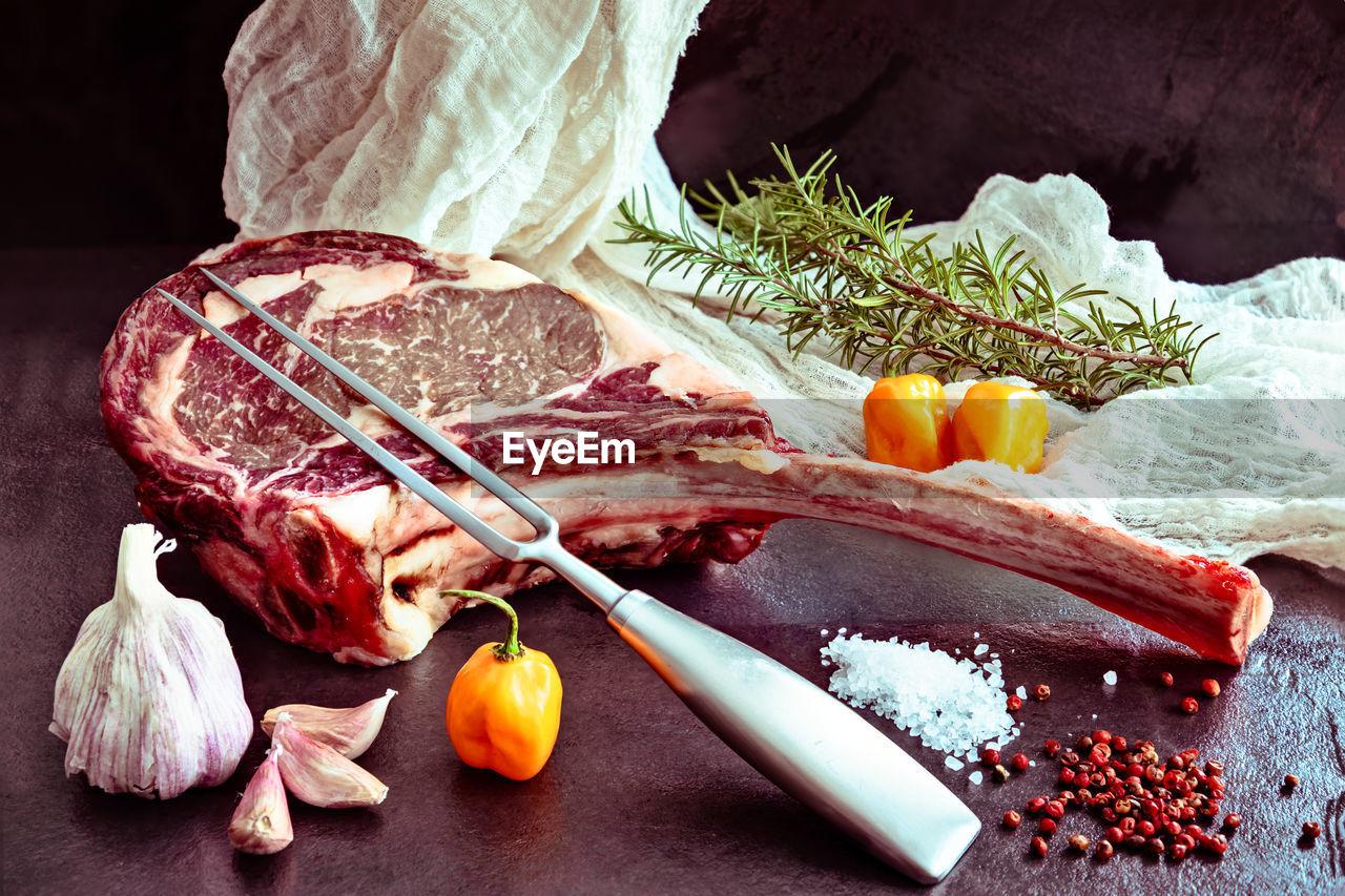 Raw ,dry-aged wagyu tomahawk steak with rosemary, salt, pepper, garlic, habanero pepper