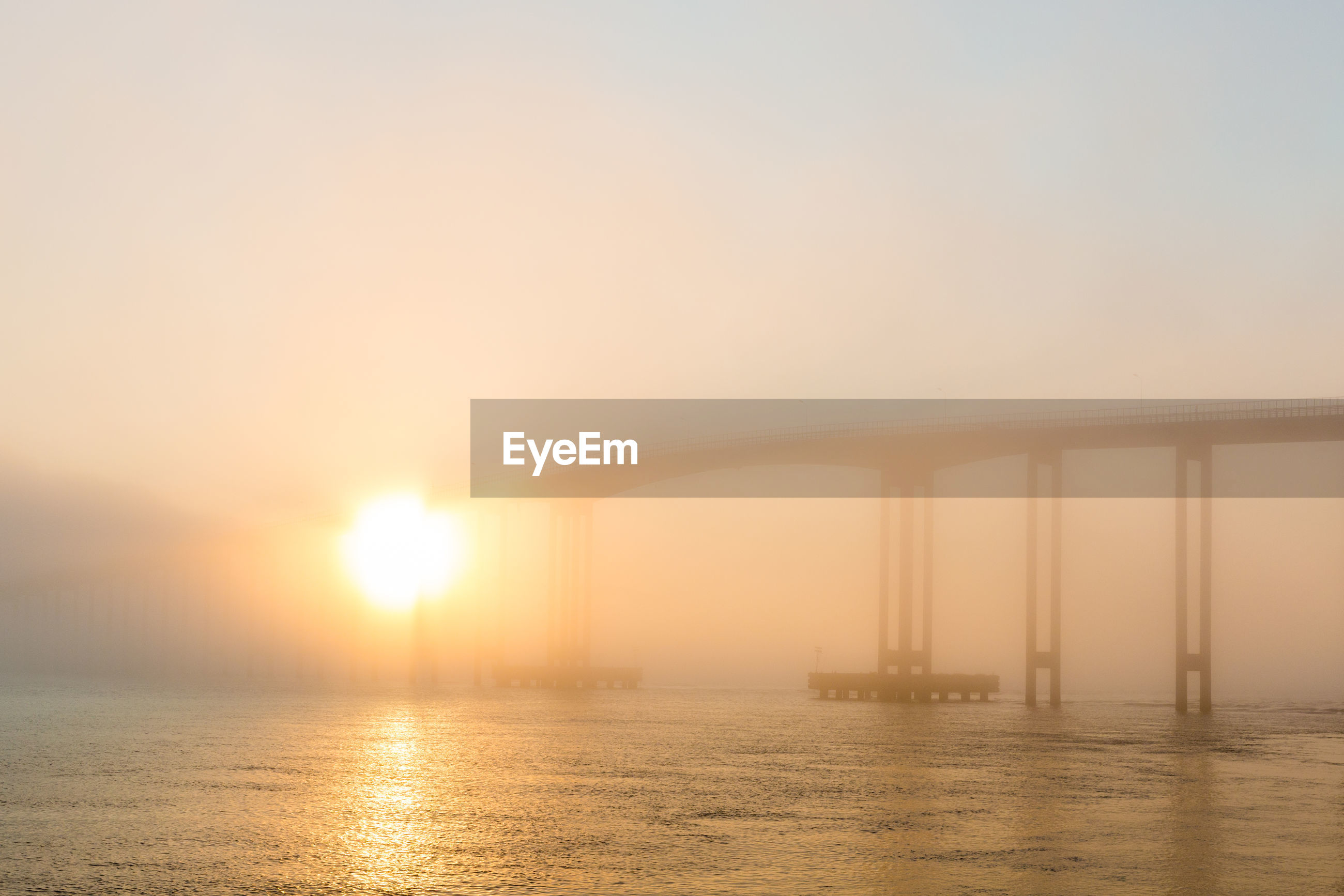 Bridge over river in foggy weather during sunset