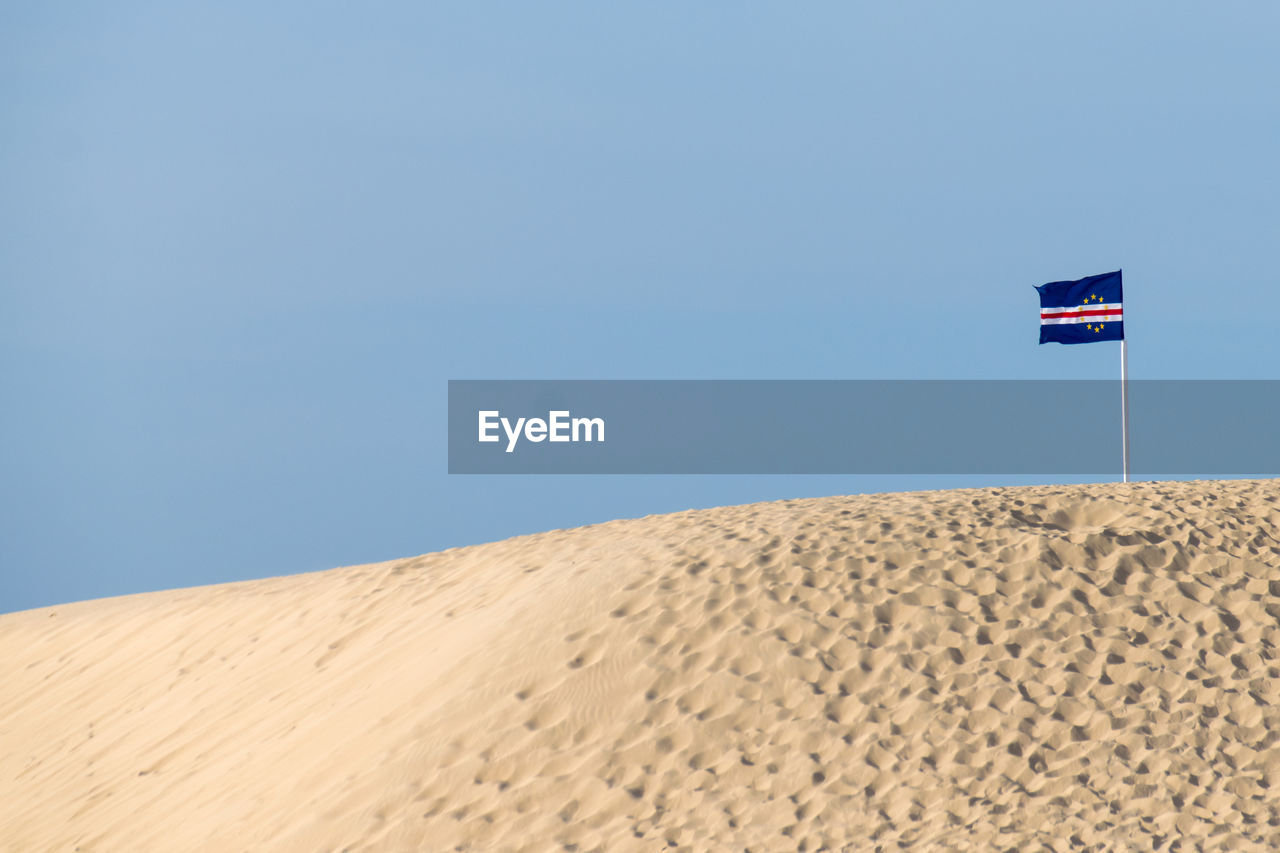 land, sand, sky, scenics - nature, flag, patriotism, blue, nature, landscape, environment, desert, arid climate, climate, day, clear sky, tranquil scene, copy space, beauty in nature, sand dune, no people, outdoors, wind