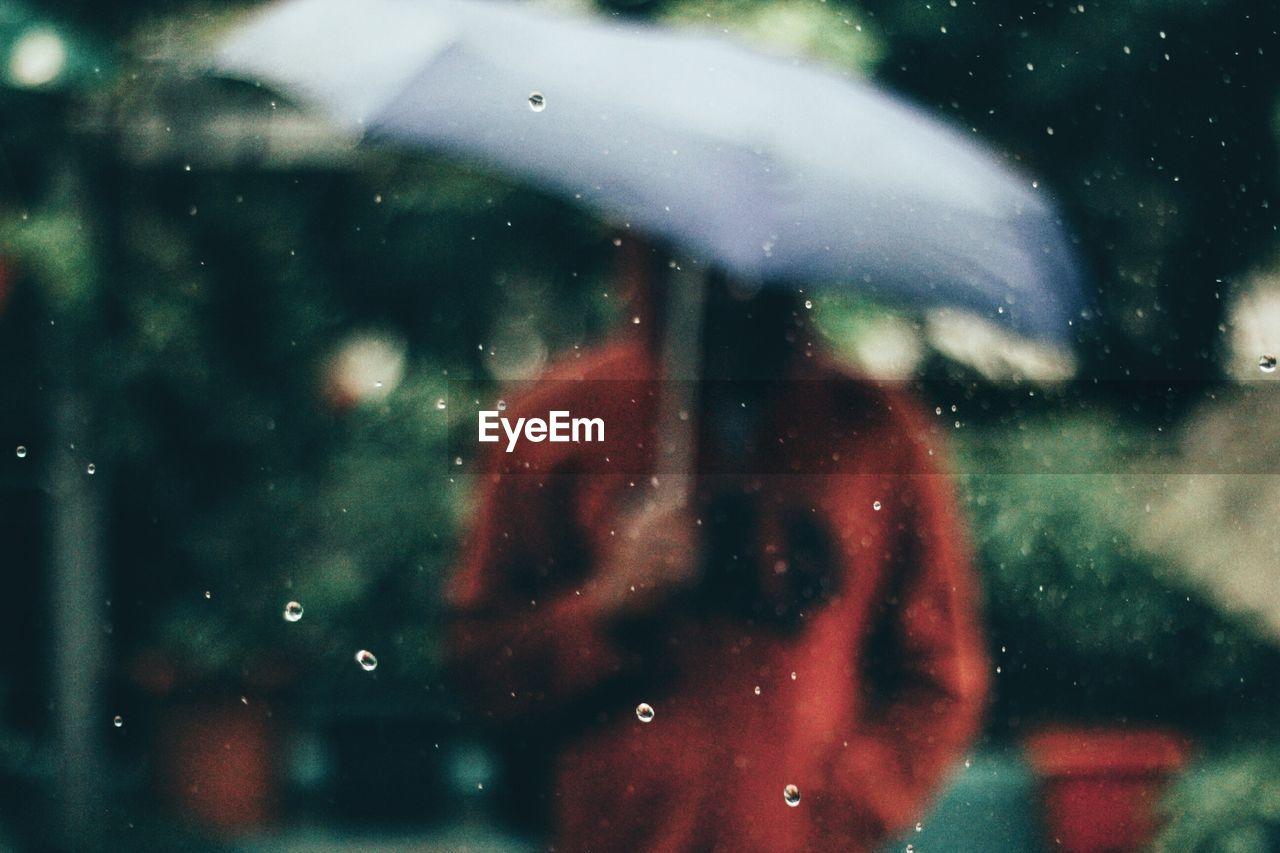 Man holding umbrella seen through window during rainy season