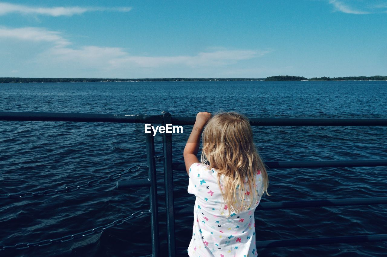 water, sea, one person, child, sky, childhood, leisure activity, real people, women, girls, nature, day, railing, beauty in nature, lifestyles, rear view, standing, horizon, females, outdoors, hairstyle, hair, horizon over water, innocence