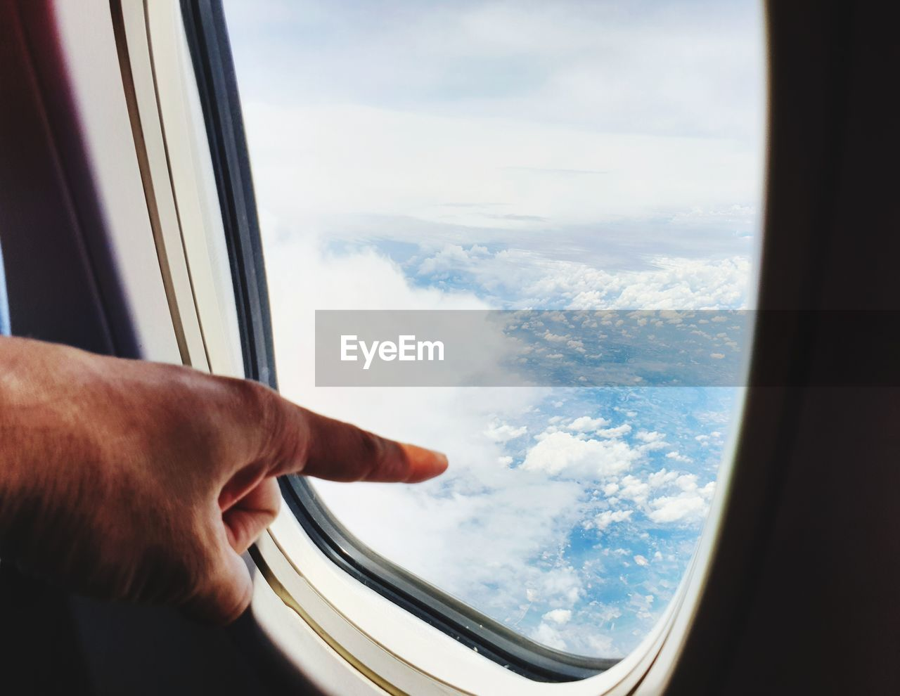 Cropped hand of person gesturing by airplane window