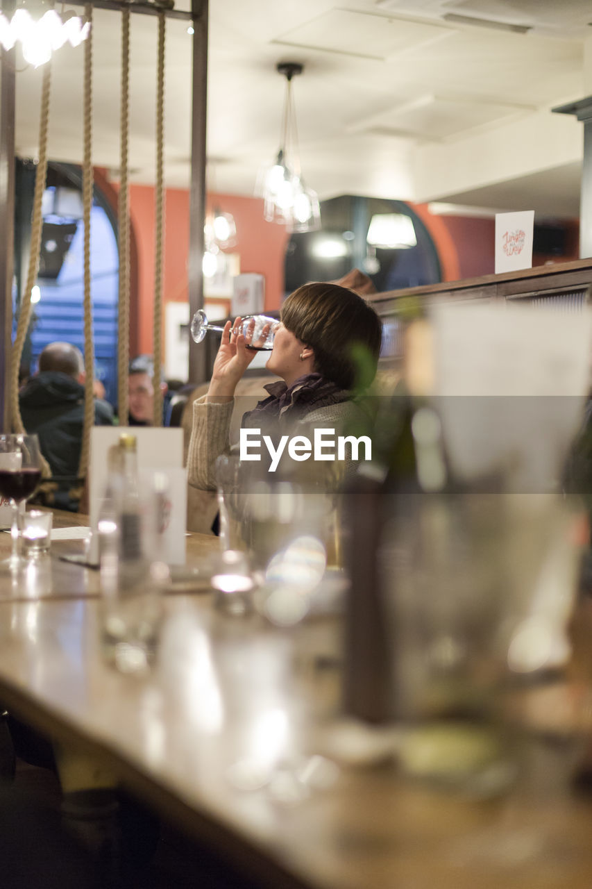 Man drinking wine at table in restaurant