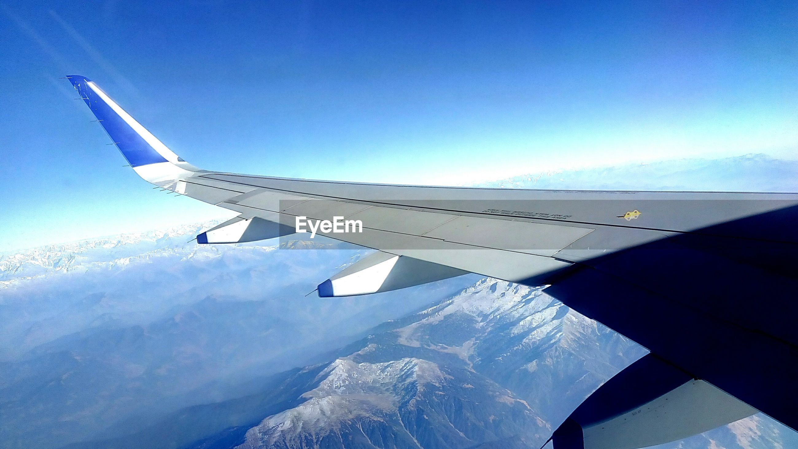 airplane, aerial view, sky, transportation, airplane wing, day, blue, nature, cloud - sky, journey, scenics, travel, aircraft wing, no people, air vehicle, mountain, beauty in nature, snow, cold temperature, outdoors, landscape, mountain range, flying