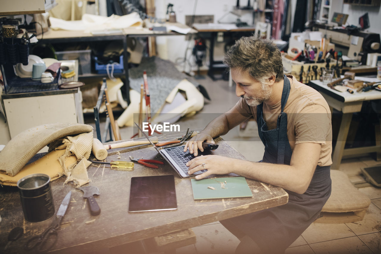 one person, working, workshop, concentration, indoors, real people, adult, occupation, technology, sitting, mid adult, craft, waist up, casual clothing, skill, art and craft, focus on foreground, business, small business, workbench, using laptop, hairstyle