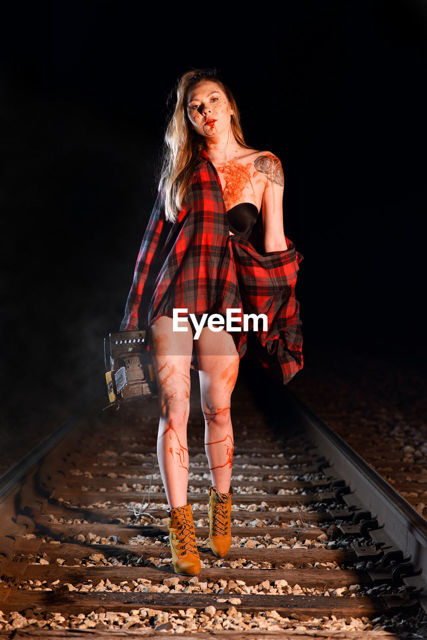 Portrait Of Young Woman With Chainsaw Walking On Railroad Track