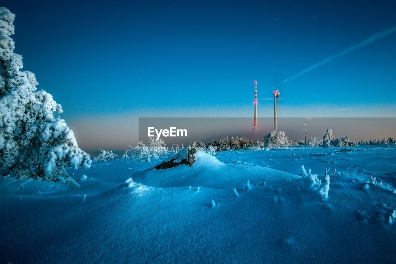 Scenic View Of Snow Covered Field Against Sky At Dusk