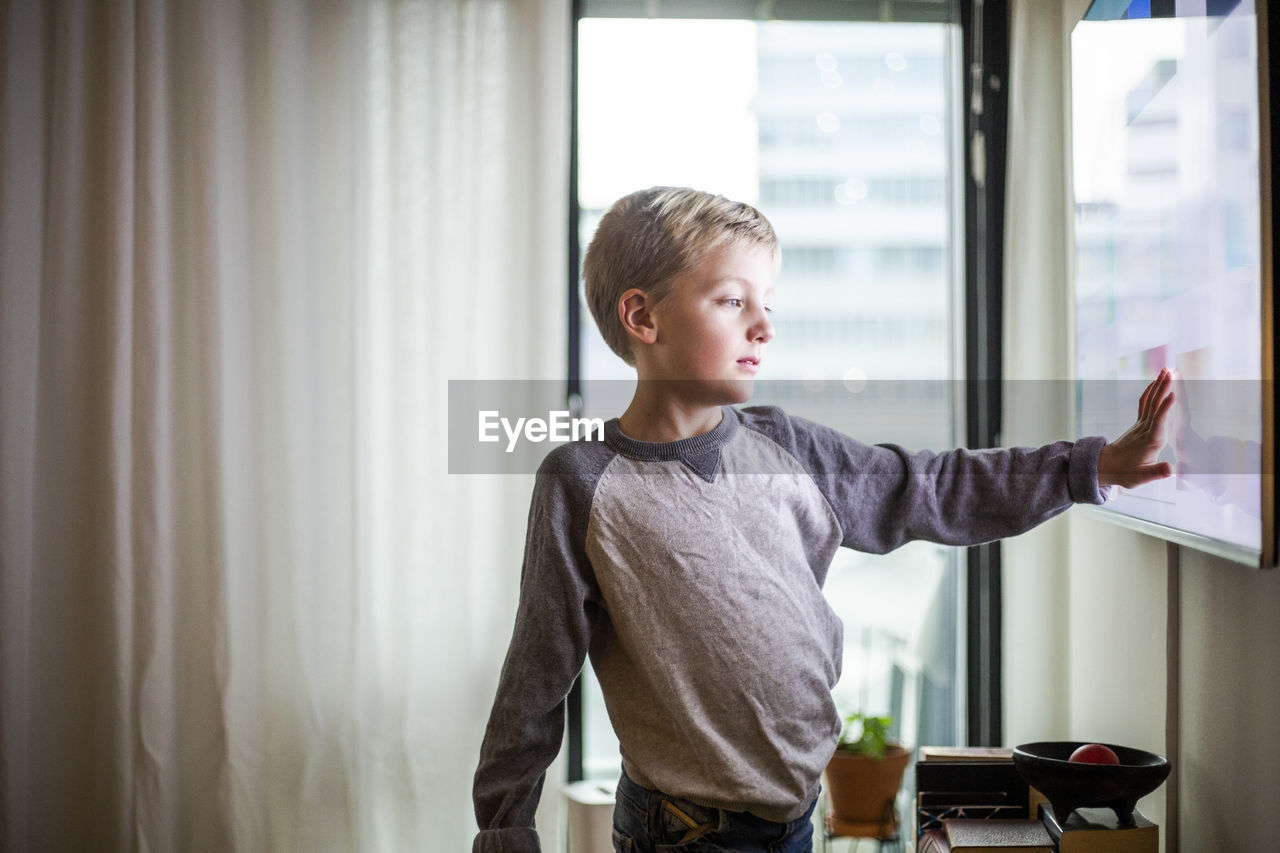 FULL LENGTH OF BOY LOOKING AT WINDOW