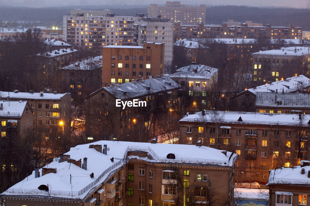 Snow Covered Buildings In City At Dusk