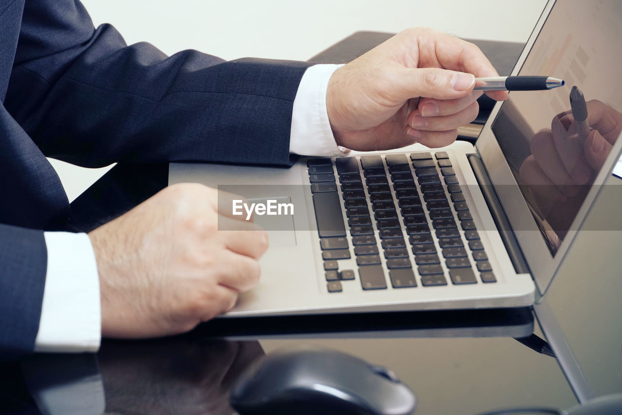real people, technology, computer, laptop, human hand, communication, men, wireless technology, one person, hand, connection, business, table, human body part, adult, portable information device, businessman, midsection, indoors, using laptop, keyboard