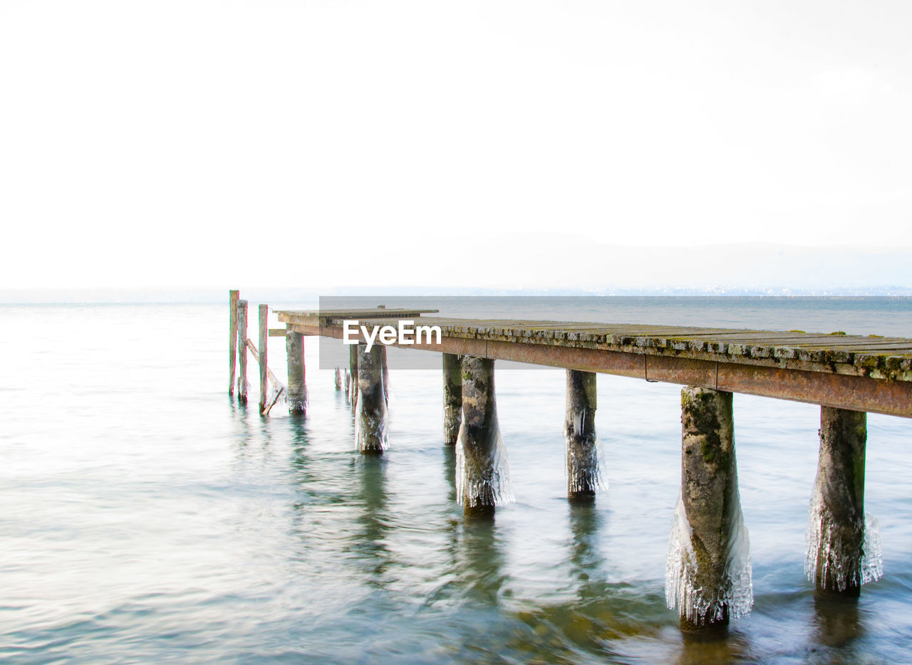 water, sea, sky, pier, wood - material, no people, horizon, day, waterfront, tranquility, tranquil scene, nature, scenics - nature, horizon over water, built structure, architectural column, clear sky, text, beach, outdoors, post, wooden post