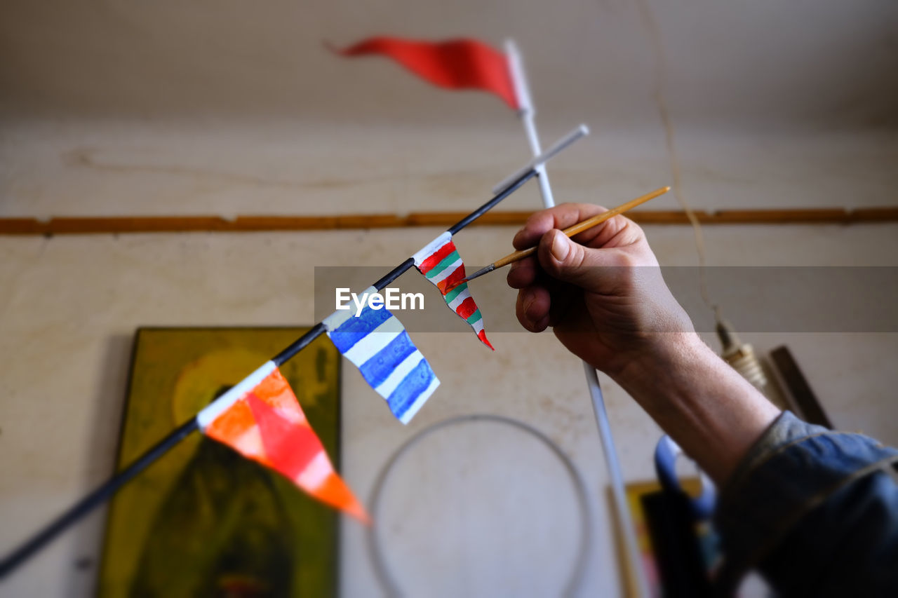 MIDSECTION OF MAN HOLDING FLAG IN THE WALL