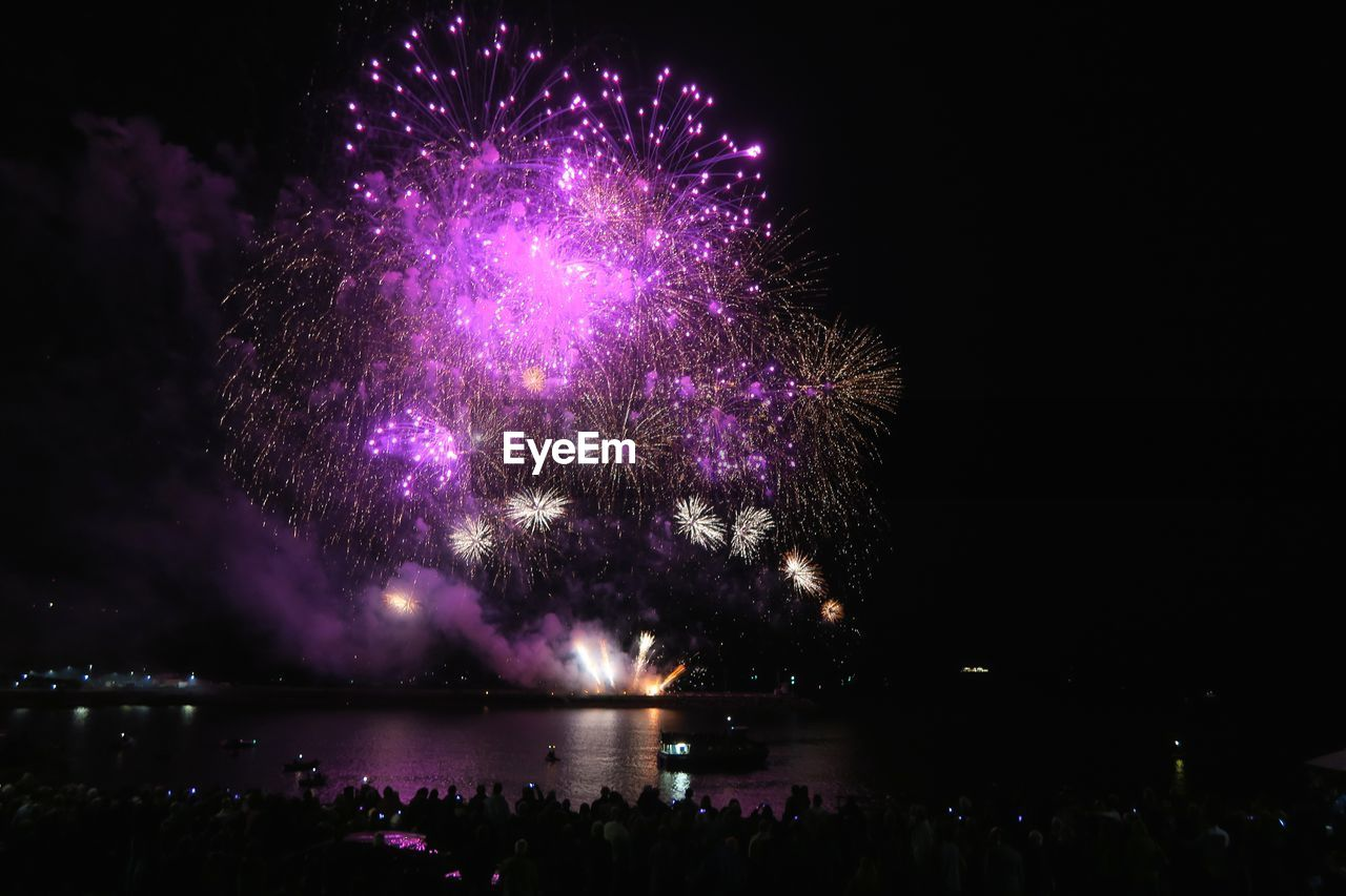 night, illuminated, celebration, event, firework, arts culture and entertainment, sky, firework display, nature, water, motion, exploding, light, glowing, silhouette, outdoors, low angle view, no people, purple, firework - man made object