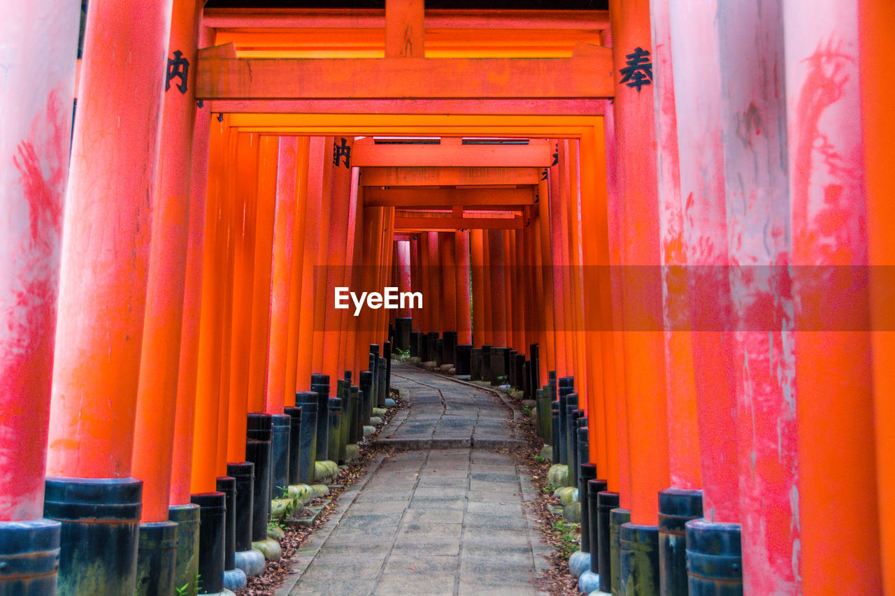 religion, place of worship, architecture, belief, built structure, spirituality, in a row, direction, the way forward, diminishing perspective, shrine, architectural column, travel destinations, orange color, building, travel, no people, colonnade