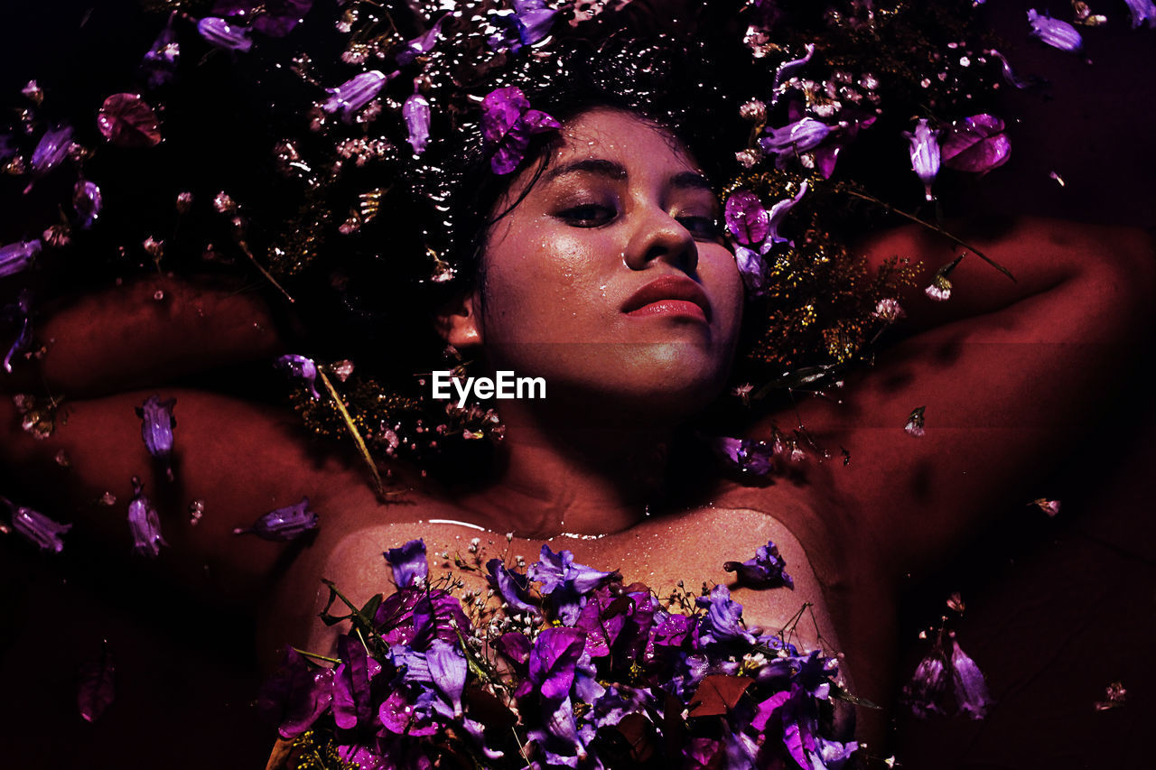 Portrait of shirtless young woman with purple flowers in water