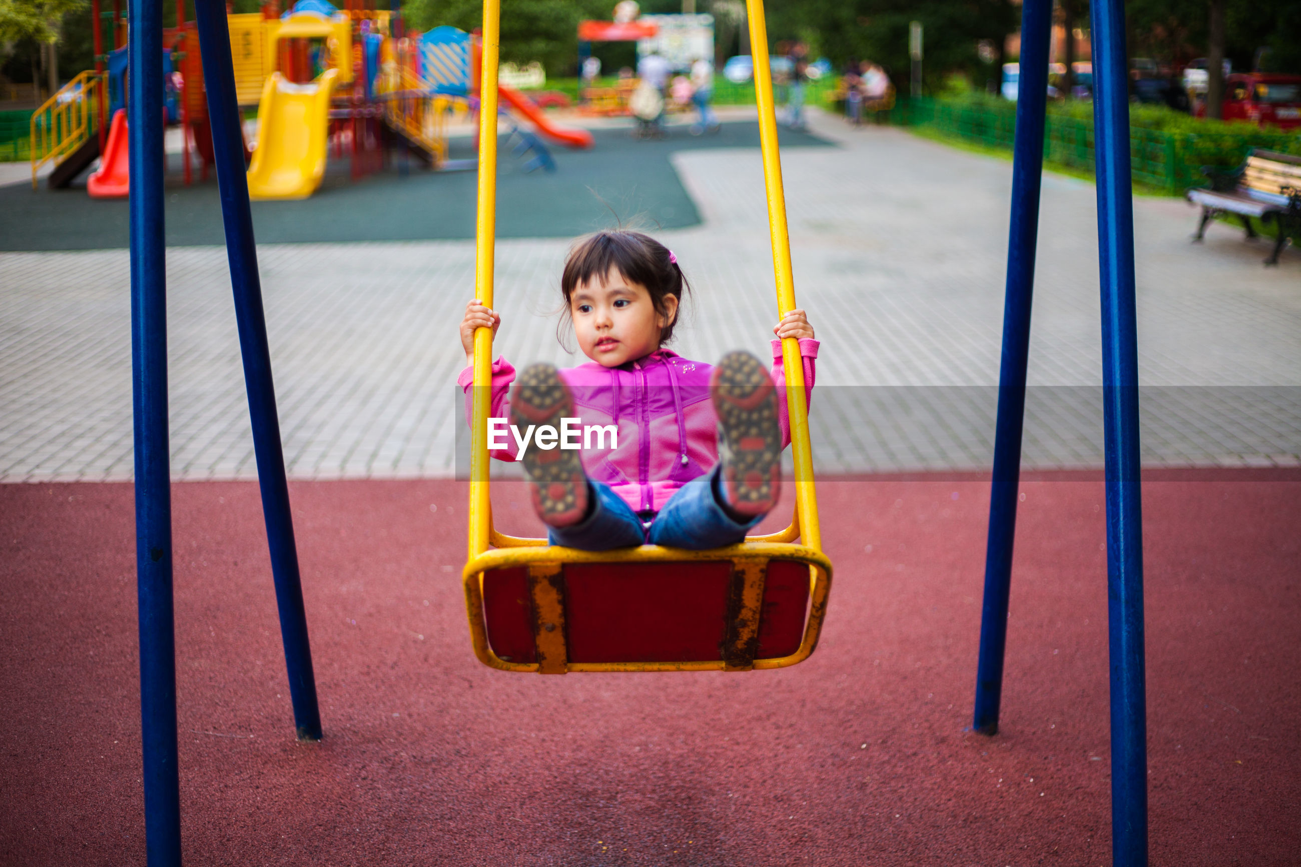 Cute girl swinging on swing in playground
