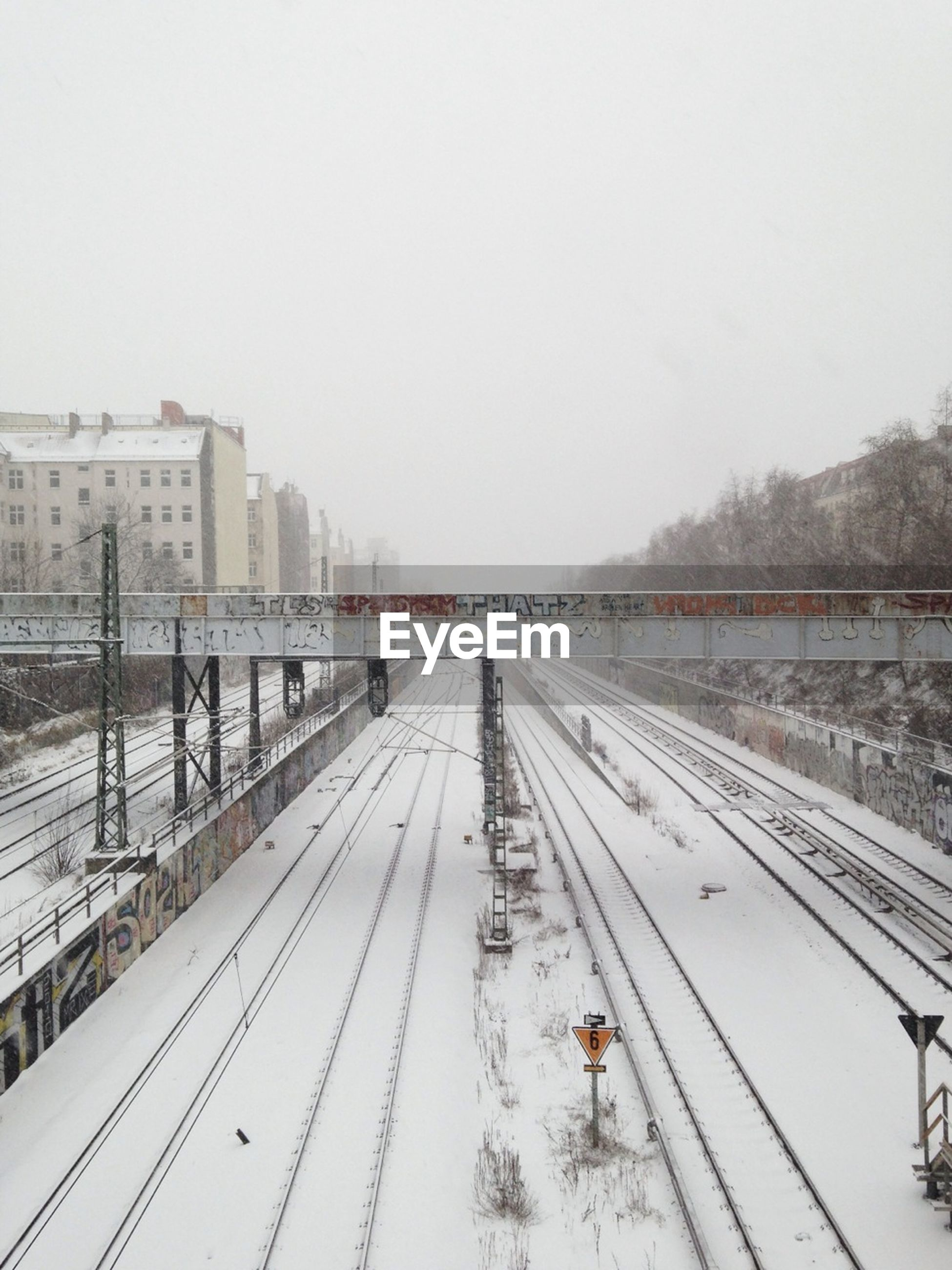 High angle view of snow covered railroad tracks against clear sky