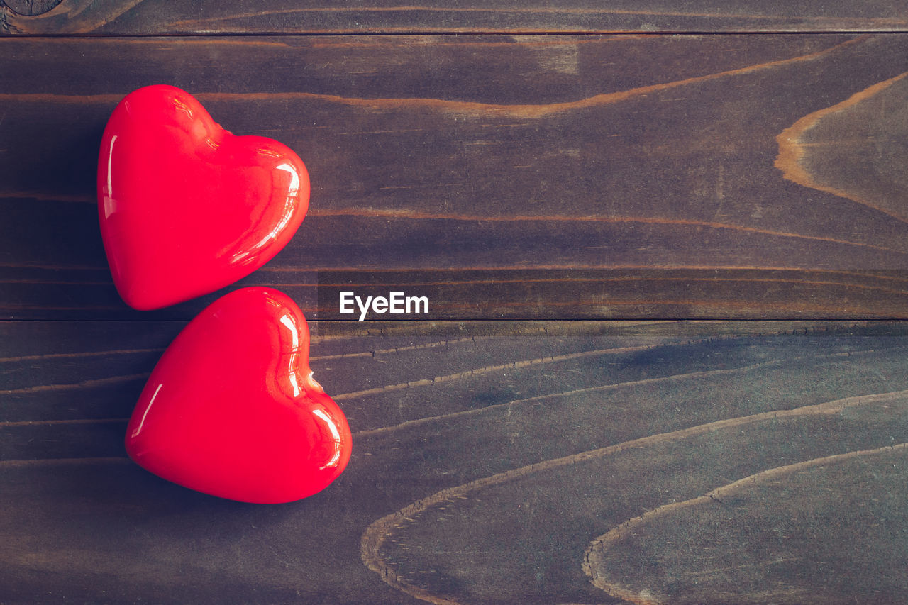 red, indoors, still life, no people, wood - material, high angle view, close-up, table, two objects, heart shape, shoe, balloon, positive emotion, flooring, single object, wood, love, container, toy, leather