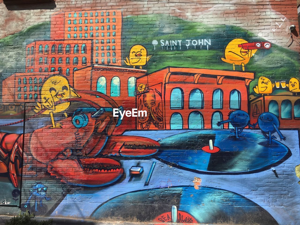 art and craft, text, creativity, graffiti, communication, multi colored, western script, representation, street art, human representation, architecture, built structure, wall - building feature, city, day, no people, male likeness, wall, script, outdoors, mural
