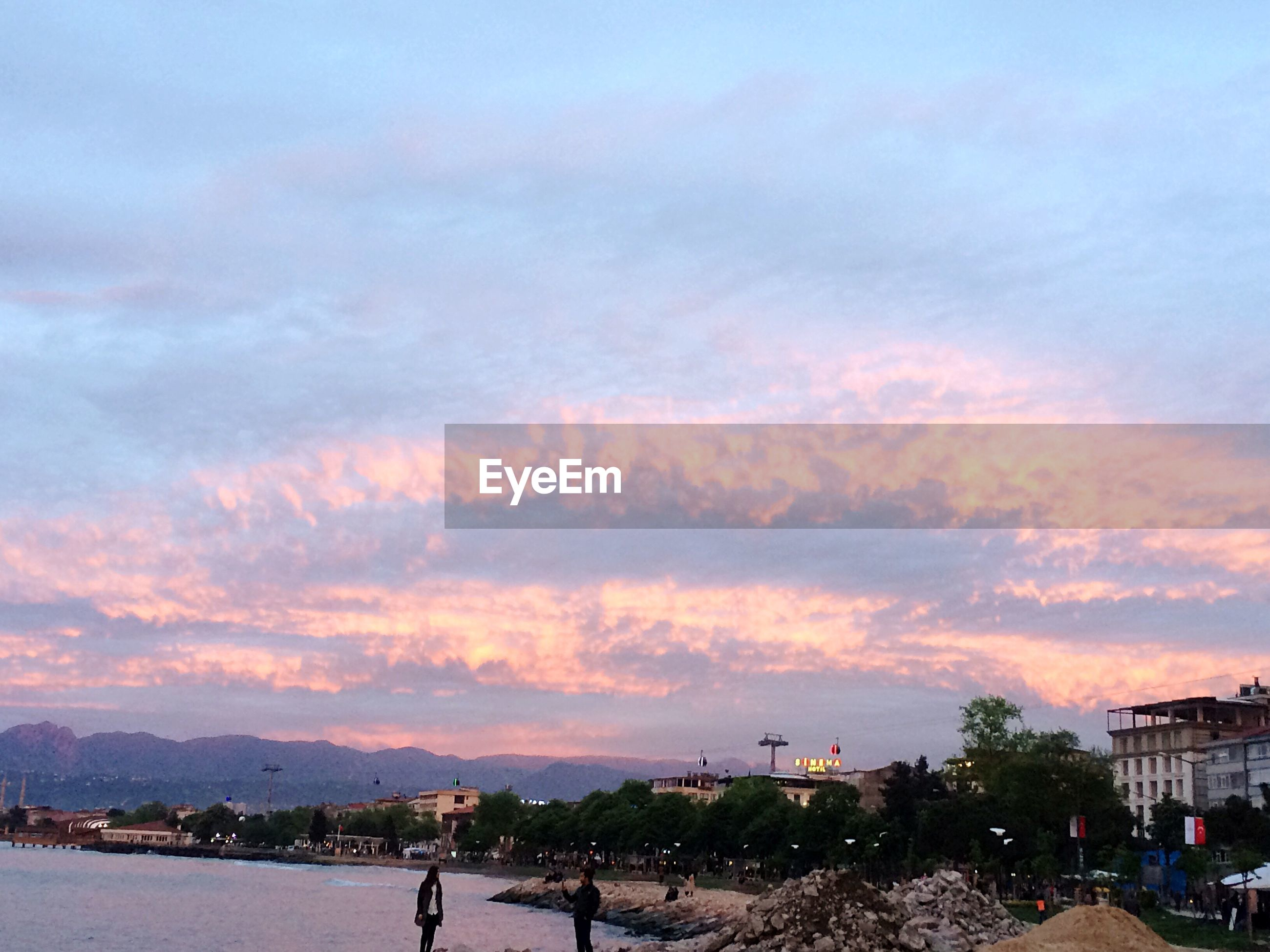 sky, cloud - sky, sunset, built structure, real people, outdoors, building exterior, architecture, nature, tree, large group of people, men, beauty in nature, beach, scenics, women, city, water, day, people