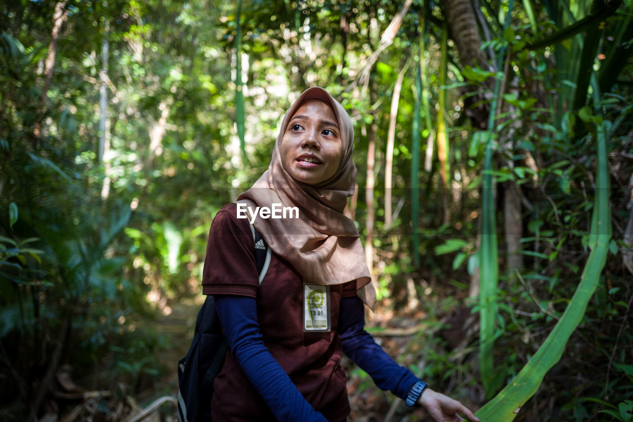 forest, tree, land, young adult, three quarter length, one person, plant, portrait, looking at camera, real people, casual clothing, leisure activity, lifestyles, adult, nature, smiling, front view, sitting, outdoors, woodland, contemplation, beautiful woman